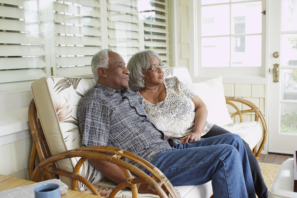 Mature black couple sitting on couch looking away